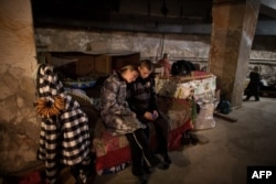 Residents of the Prtrovskyi neighborhood of the city of Donetsk sit in a bomb shelter last November.