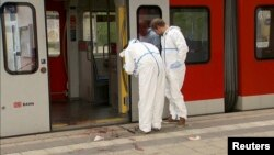 Germany -- Police investigators looks at bloodstained footprints leading out of a train and on a platform following a knife attack in Grafing train station, south east of Munich, May 10, 2016