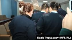 Айдауыл Василина Соколенконың қолына кісен салып, сот залынан әкетіп барады. Алматы, 22 қазан 2018 жыл.