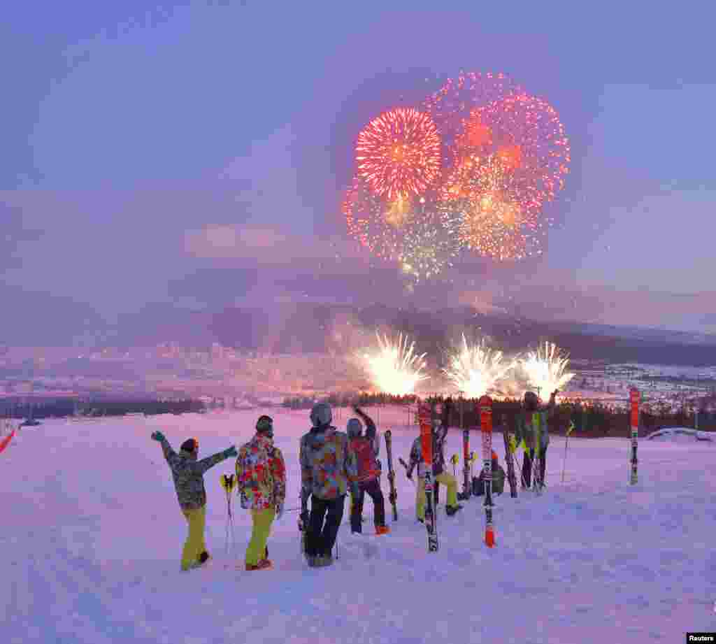 Skiers watch the fireworks at dusk during the opening ceremony.