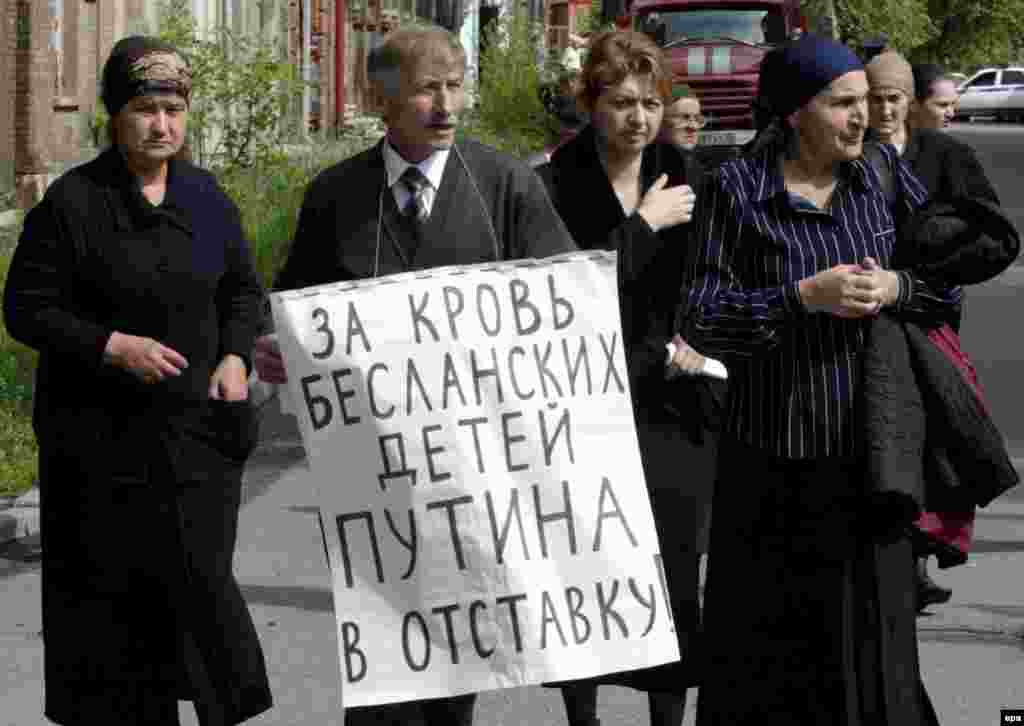 Beslan relatives demonstrate outside the Kulayev trial in May 2006, holding anti-Putin placards (epa) - Survivors are not alone in distrusting authorities over Beslan. A poll published last week by Russia's Levada Center found that only 8 percent of respondents believe the government has told the whole truth.