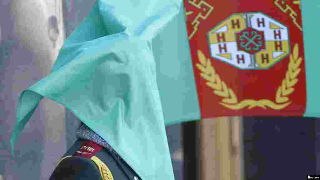 A Ukrainian honor guard's face is covered by the Turkmen flag during an official welcoming ceremony for the Turkmen president in Kyiv. (Reuters/Gleb Garanich)