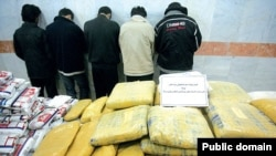 A pile of drugs is displayed in front of a group of suspected drug traffickers arrested in Iran.