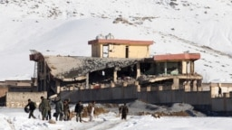 Afghan intelligence officers leave the collapsed building of the military base following an attack in Maidan Wardak on January 21.