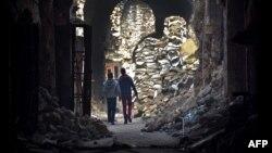 Сирияның Алеппо қаласындағы соғыстан қираған ғимараттың қасынан өтіп бара жатқан адамдар. 19 қаңтар 2017 жыл.