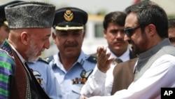 Ауғанстан президенті Хамид Қарзайды (сол жақта) Пәкістанның спорт министрі Шаукатулла қарсы алып тұр. Чаклала әуе базасы, Равалпинди, Пәкістан. 10 маусым 2011 ж.