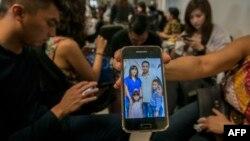 یکی از بستگان مسافران هواپیما تصویری از اعضای خانوادهای که در ایرباس «ایر-آسیا» بودهاند را در فرودگاه سورابایا، مبدا پرواز، به خبرنگاران نشان میدهد