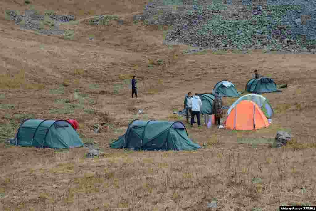 На этом фото – палаточный лагерь участников Beken Ata Expeditions: Sacred QyzEmshek. Рядом с лагерем протекает ручей, который едва просматривается под густо поросшей вдоль него травой. Считается, что именно наличие здесь воды привлекает диких животных. А вслед за ними сюда шли люди древних эпох, чей быт и чью культуру наши современники пытаются реконструировать. Высота над уровнем – моря 3000–3100 метров. Хотя это место считается относительно защищенным от сильных ветров, условия для проживания здесь довольно суровые. Ночью в емкостях с водой образовывались куски льда. Несколько раз местность и лагерь накрывало дождем или мокрым снегом. В первый день участники экспедиции археологией не занимались. Они осваивались, привыкали к месту временного пребывания.