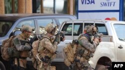 French special forces take position around the Splendid hotel following an attack by Al-Qaeda linked gunmen on January 16. Twenty-nine people were killed in the assault.