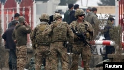 U.S. troops stand guard at the site of a suicide attack in Kabul on February 20.