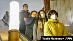 Люди у захисних масках спускаються на ескалаторі в метро (ілюстративне фото)
