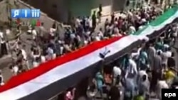 Protesters hold a giant current Syrian national flag (red, white, black) and a former national flag (green, white, black) during a protest allegedly in Palmyra, in the Homs district, on September 2.