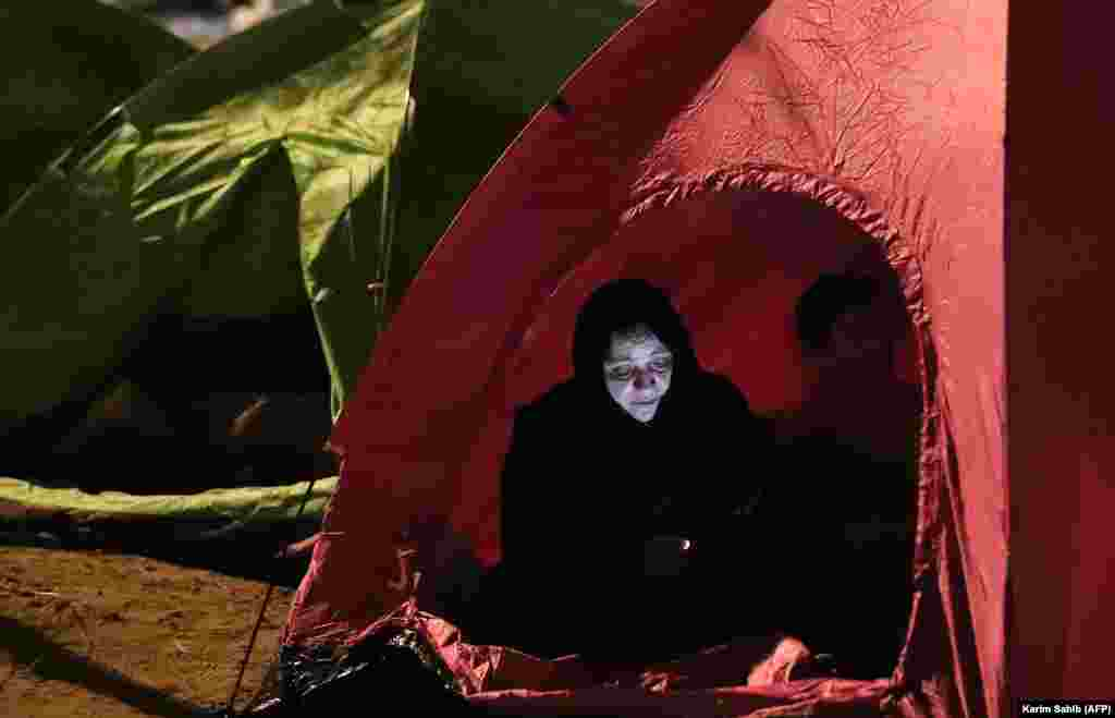 A Muslim pilgrim checks her mobile phone as she rests in a tent near Mount Arafat, also known as Jabal al-Rahma (Mount of Mercy), southeast of the Saudi holy city of Mecca on August 31. (AFP/Karim Sahib)