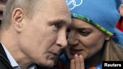 President Vladimir Putin speaks with Olympic Village Mayor and world-record pole vaultet Yelena Isinbayeva Sochi on February 5 ahead of the Winter Olympics.