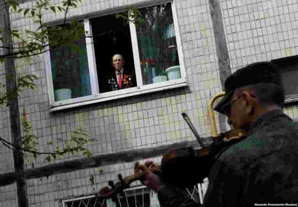 A 96-year-old World War II veteran watches from his apartment window as a band plays in his honor during Victory Day celebrations on May 9 in Donetsk, Ukraine.