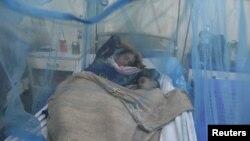 Жінка спить під москітною сіткою зі своїм дворічним сином, що захворів на гарячку денге, у відділенні місцевої лікарні в Равалпінді (фото архівне)