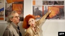 """22.11.2004 г. Кристо и Жан-Клод представят проекта си """"Портите"""" в Сентръл парк в Ню Йорк. Той включва изграждането на 7500 порти в златисто-оранжев цвят над пешеходните алеи на парка."""