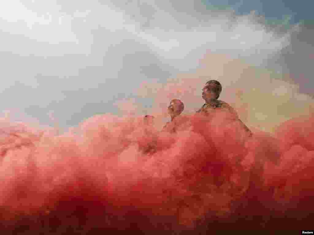 Afghan National Army noncommissioned-officer recruits march through colored smoke during a parade to mark a graduation ceremony at the Turkish-run Camp Ghazi in Kabul on March 31. Photo by Ahmad Masood for Reuters