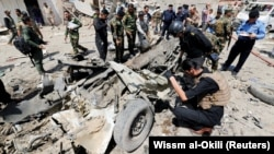Iraqi security forces inspect the site of a car-bomb attack in a Baghdad neighborhood on August 28.