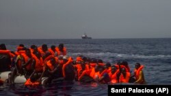 Люди в воде в спасательных жилетах. Иллюстративное фото.