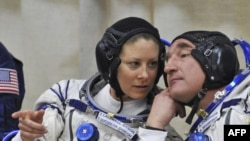 Tracy Caldwell Dyson consults with her Russian shipmate Alexander Skvortsov before the Soyuz lift-off on April 2.