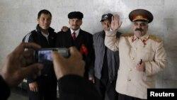 Мигранты фотографируются с людьми, изображающими Ленина и Сталина, Москва, 6 октября 2011 года.