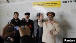 Трудовые мигранты из Центральной Азии фотографируются на память с людьми, изображающими Ленина и Сталина. Москва, 6 октября 2011 года.
