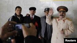 Ресейде жүрген шетелдік жұмысшылар Ленин мен Сталин болып киініп алған адамдардың қасында суретке түсіп тұр. Мәскеу, 6 қазан 2011 жыл.