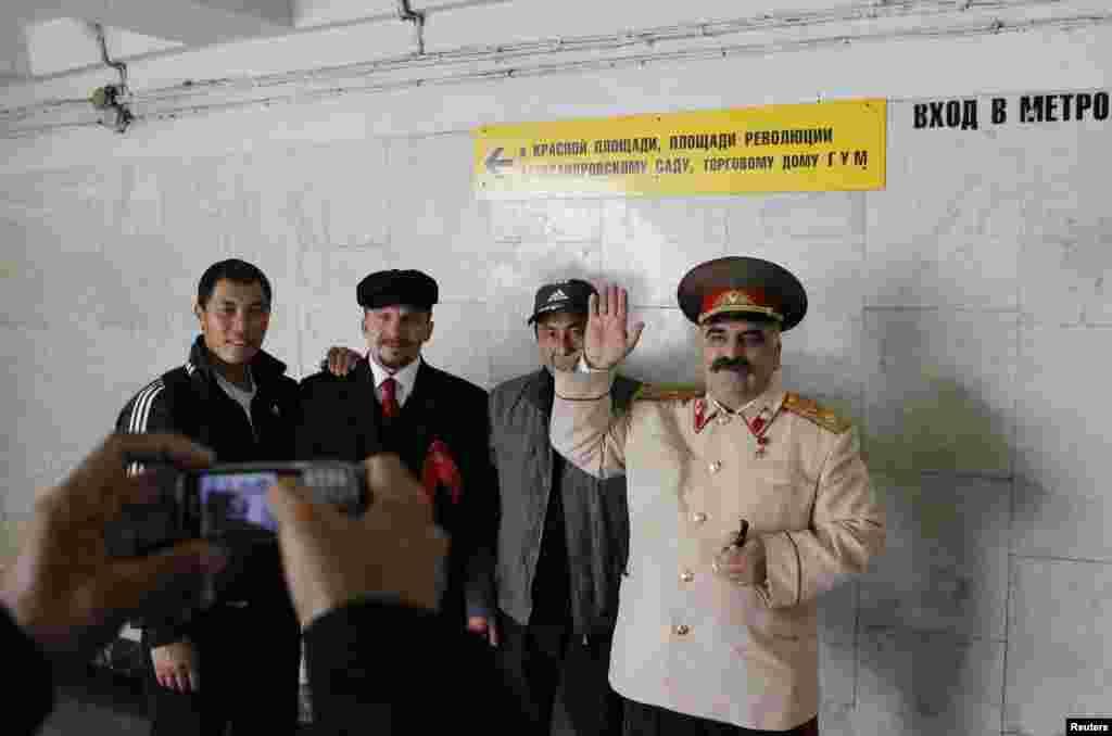 Трудовые мигранты фотографируются с двойниками Ленина и Сталина в Москве. 2011.