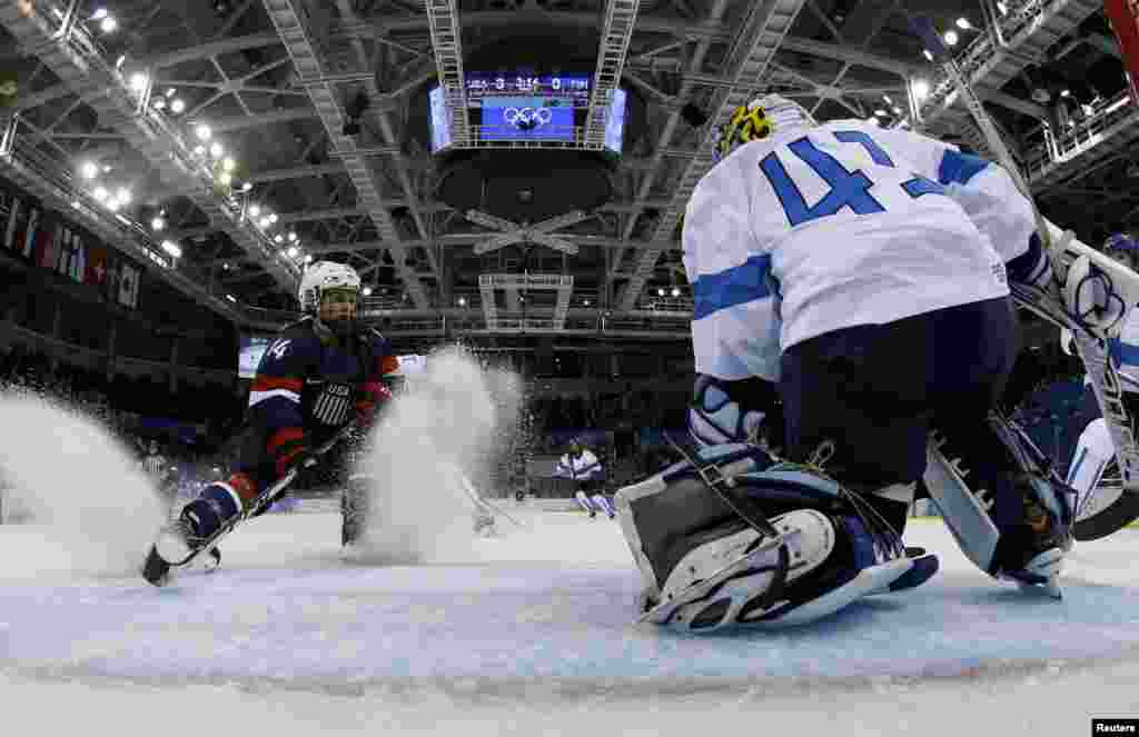 The United States' Brianna Decker (left) goes one on one with Finland's goalkeeper Noora Raty during the second period of their women's preliminary round ice-hockey game.