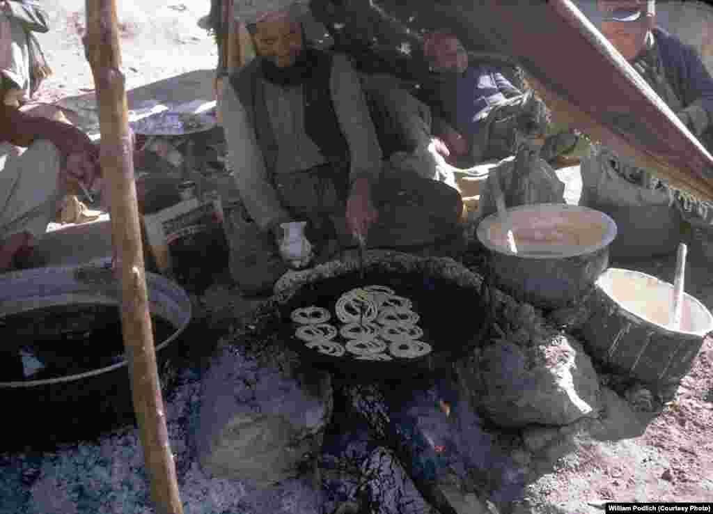 A merchant fries jalebi, a sweet Afghan dessert, over an open fire.