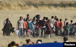 """Сирийские курды, бегущие через границу с Турцией от боевиков """"Исламского государства"""". Июнь 2015 года"""