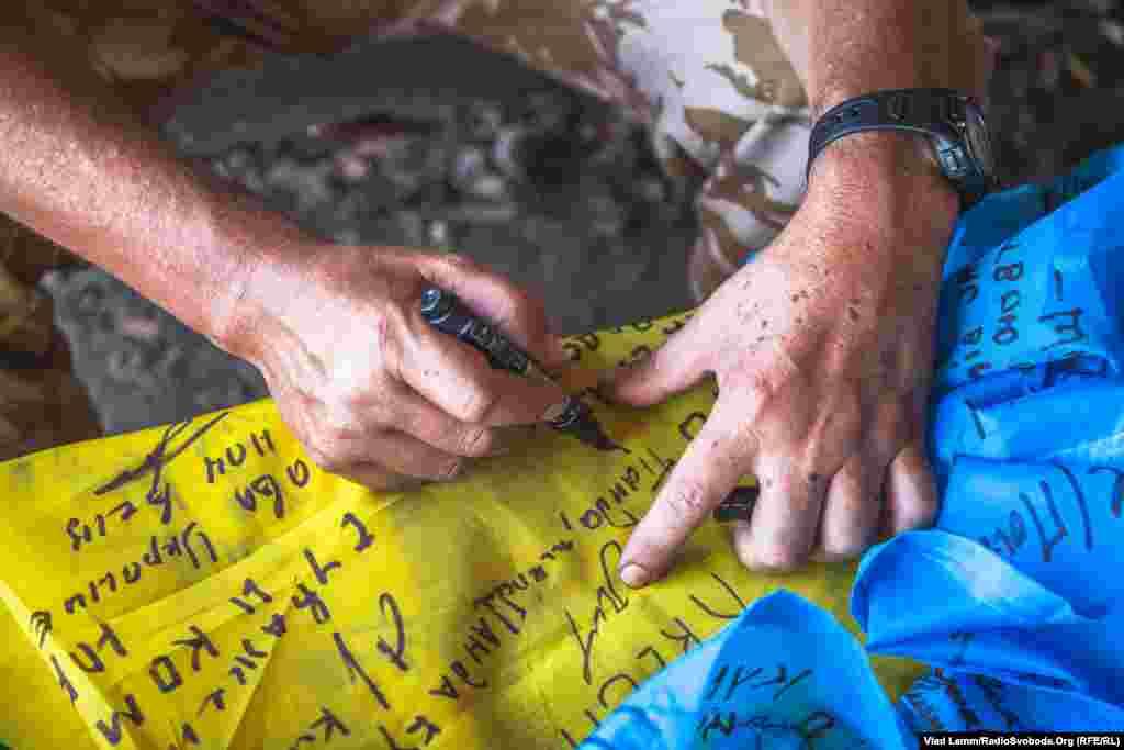 Боєць з позивним «Бек» підписує прапор демобілізованним побратимам