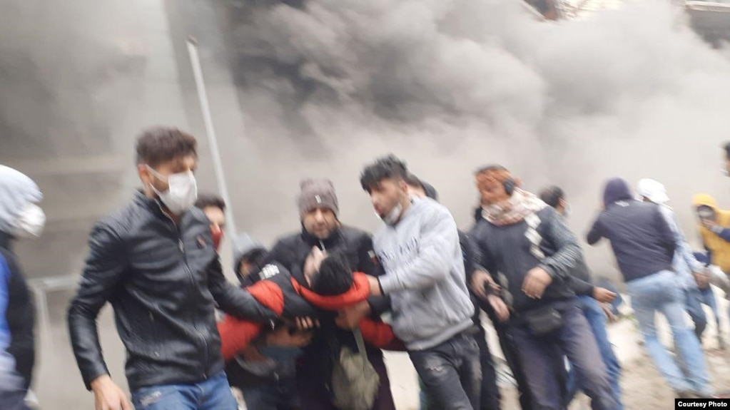 Young protesters carrying away a comrade during fierce protests in Shiraz, Iran. November 2019