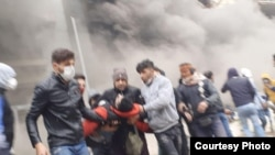 Iranian protesters carrying away a wounded comrade. November 17, 2019