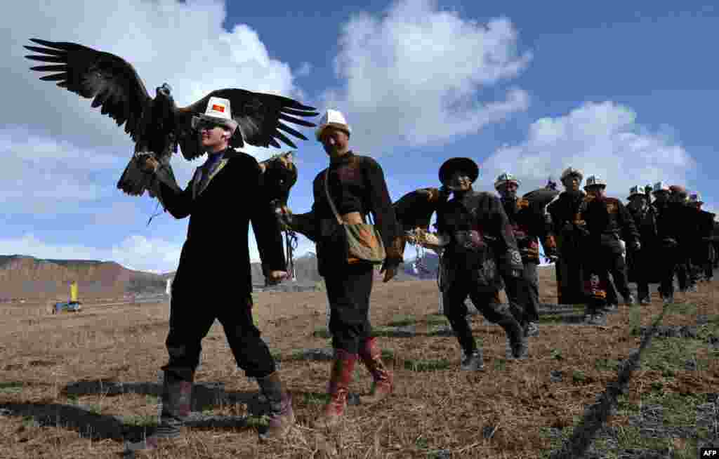 Kyrgyz berkutchi, or eagle hunters, carry their golden eagles during a hunting festival called Salburun in the village of Alysh, near Naryn, 350 kilometers outside Bishkek. (AFP/Vyacheslav Oseledko)