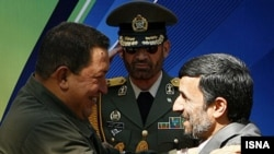 Deadly embrace? Venezuela's Hugo Chavez and Iran's Mahmud Ahmadinejad at a welcoming ceremony in Tehran in April 2009.