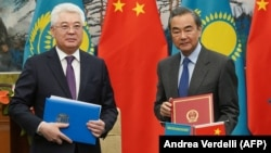 Kazakh Foreign Minister Beibut Atamkulov (left) and Chinese Foreign Minister Wang Yi attend a signing ceremony at the Diaoyutai State Guesthouse in Beijing on March 28.