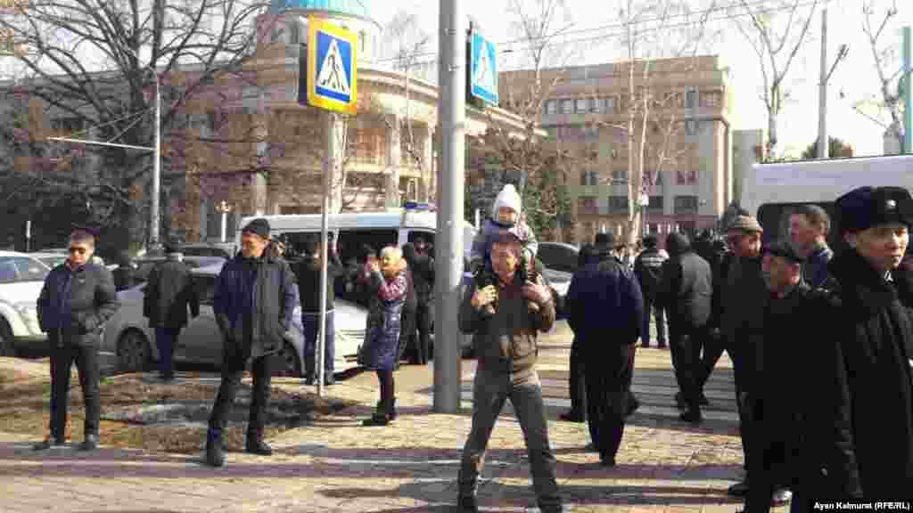 Партия кеңсесі маңынан өтіп бара жатқан тұрғындар оқиғаны бақылап тұр.