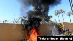 Forțe paramilitare dând foc unui zid al sediului ambasadei americane din Bagdad. 31 decembrie 2019