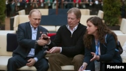 Russian President Vladimir Putin (left) and U.S. Olympic Committee Chairman Larry Probst (center) at USA House in the Olympic Village during the 2014 Sochi Winter Olympics on February 14