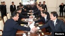 Оңтүстік және Солтүстік Кореялар делегацияларының өкілдері Пханмунджомдағы алғашқы кездесу кезінде қол алысып тұр. 9 қаңтар 2018 жыл.