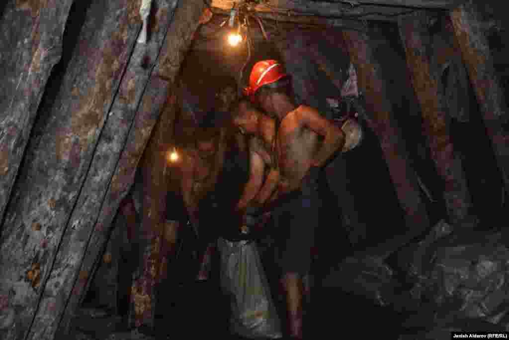 Горняки фасуют уголь в мешки.