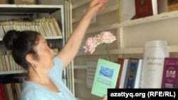 Шұбарши кентінің кітапханашысы Тыныштық Қазбекова діни әдебиеттер тұрған бұрышты көрсетіп тұр. Ақтөбе облысы, Шұбарши кенті, 14 мамыр 2012 жыл.