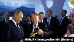 Президент России Владимир Путин и его казахстанский коллега Нурсултан Назарбаев рассматривают камчу на туристической выставке. Петропавловск, 9 ноября 2018 года.