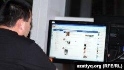 Мужчина у компьютера просматривает страницу Facebook'а.