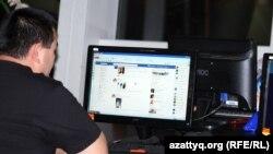 Интернет клубта Facebook әлеуметтік желісін қарап отырған адам.