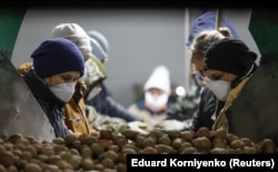 Employees wearing protective masks process potatoes in a vegetable storage in the village of Vinsady in the Stavropol region on March 27.