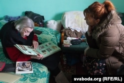 Yanina Grintsevic Stasya looking at old pictures at her home in Belarus.