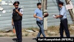 Оқиға маңындағы полицейлер мен журналист. Алматы облысы, Қарасай ауданы, 17 тамыз 2012 жыл.
